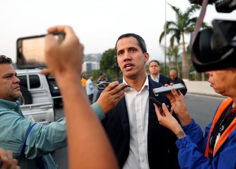 Venezuelan opposition leader Juan Guaido talks to the media outside Generalisimo Francisco de Miranda Airbase in Caracas