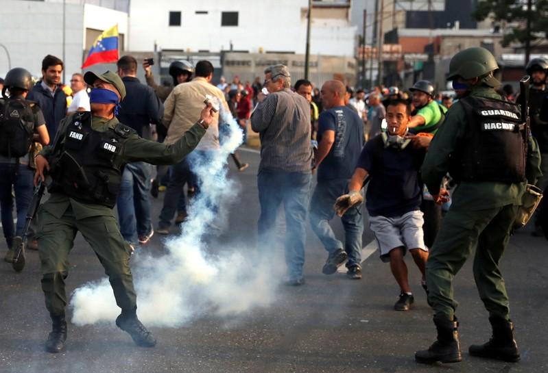 A military member throws a tear gas canister near the Generalisimo Francisco de Miranda Airbase in Caracas