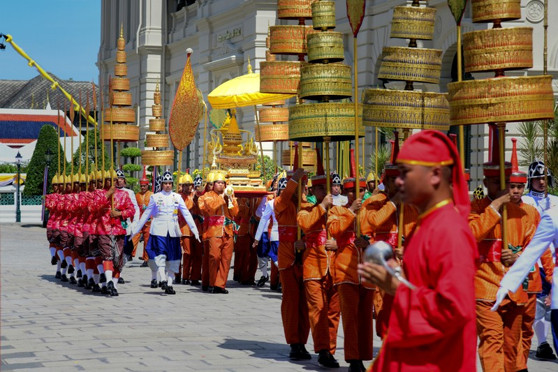Thai soldiers dressed in traditional costumes transfer The Royal Golden Plaque of the official title of His Majesty the King, the Royal Golden Plaque of His Majesty's horoscope, and the Royal Seal of State to Baisal Daksin Throne Hall at the Grand Palace