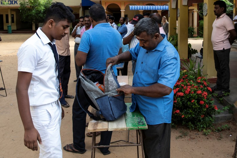 A student's bag is searched by a parent as he arrives at his school which opened days after a string of suicide bomb attacks across the island on Easter Sunday, in Batticaloa