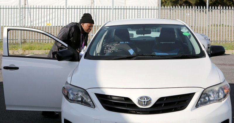 A traffic official checks an impounded Uber vehicle during a clampdown on drivers operating without permits in Cape Town