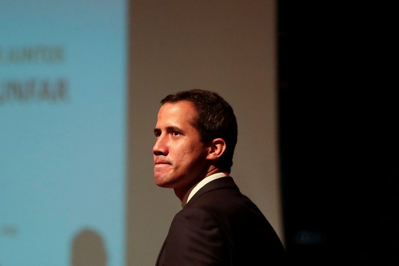 Venezuelan opposition leader Juan Guaido, who many nations have recognised as the country's rightful interim ruler, arrives on stage to deliver a speech during a meeting with workers of Venezuela's state oil company PDVSA in Caracas