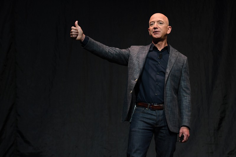 Founder, Chairman, CEO and President of Amazon Jeff Bezos gives a thumbs up as he speaks during an event about Blue Origin's space exploration plans in Washington