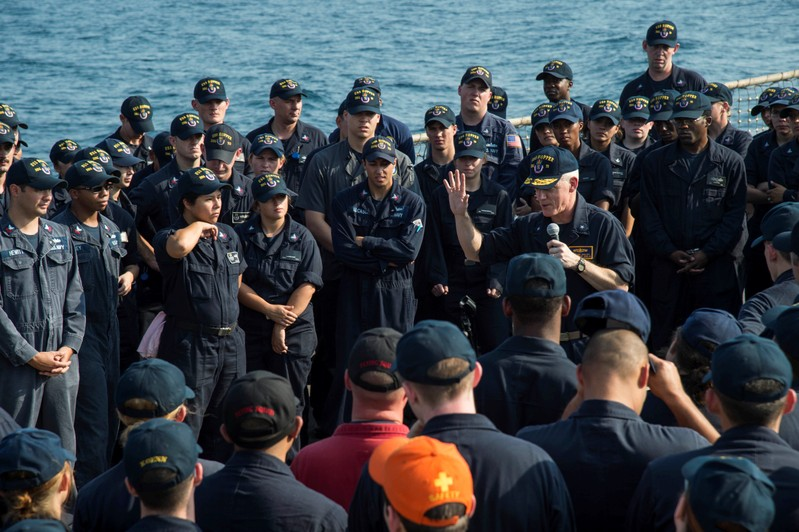 U.S. Navy Rear Admiral Jim Malloy commander Task Force 50 speaks to the crew of the guided-missile destroyer USS Hopper on the ship's flight deck at sea in the Arabian Gulf