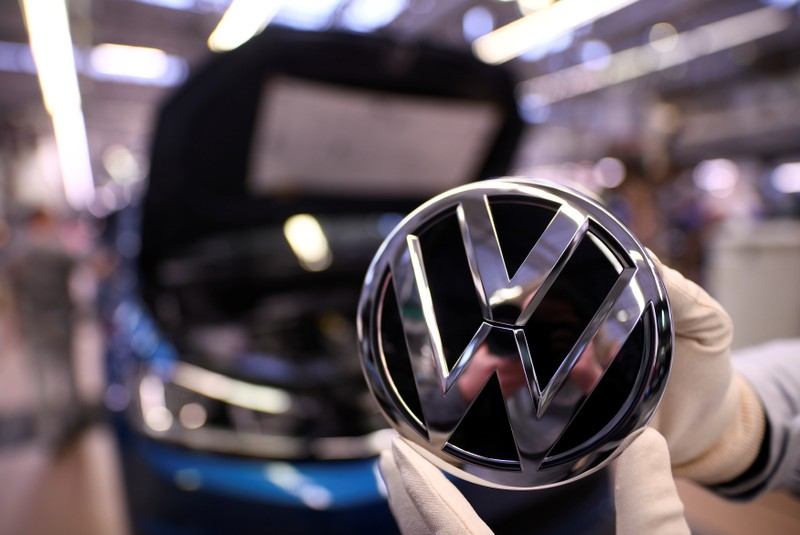 FILE PHOTO: An employee holds a Volkswagen logo in a production line at the Volkswagen plant in Wolfsburg