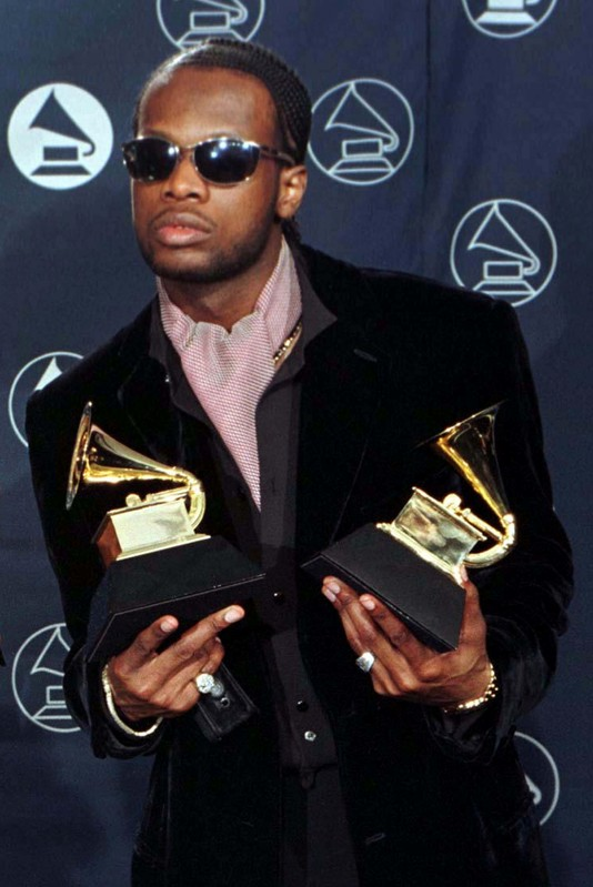 FILE PHOTO: Prakazrel Michel of the band The Fugees, poses with his Grammy awards for Best R & B Performance by a Duo or Group category for