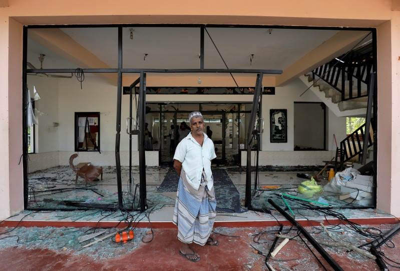 A Muslim man stands in front of the Abbraar Masjid mosque after a mob attack in Kiniyama