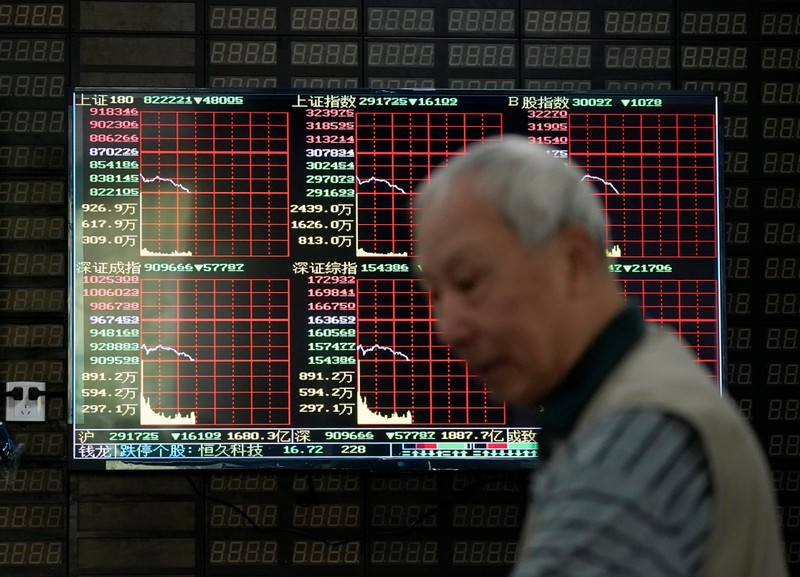 FILE PHOTO: An investor walks past a screen displaying stock information at a brokerage house in Shanghai