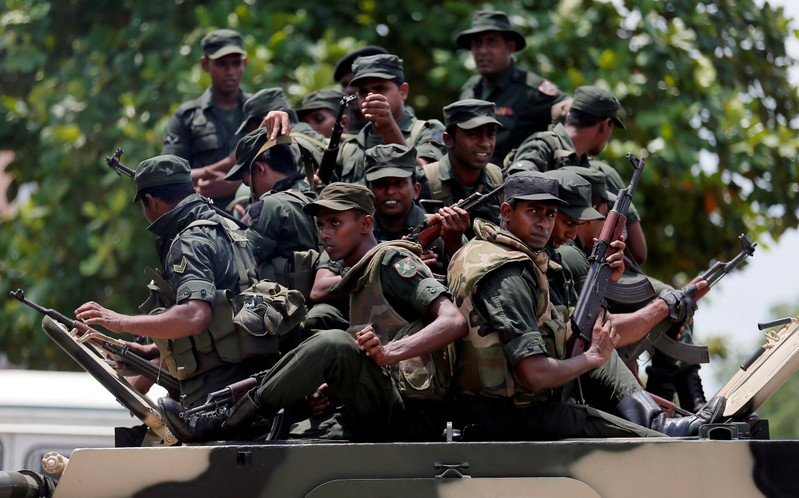 Sri Lankan soldiers patrol a road of Hettipola on top of an armored vehicle, after a mob attack in a mosque in the nearby village of Kottampitiya