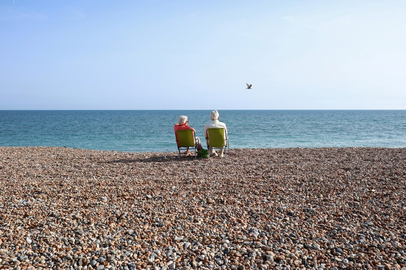 FILE PHOTO: FILE PHOTO: A couple sit on the beach and look out to sea on the August bank holiday weekend in Worthing