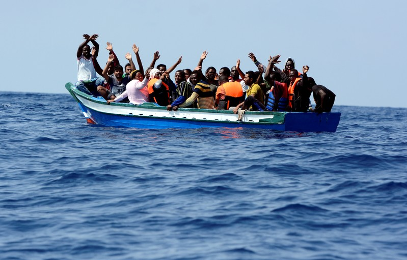 FILE PHOTO: Migrants wait to be rescued by SOS Mediterranee and Doctors Without Borders during a search and rescue operation with the MV Aquarius rescue ship in the Mediterranean