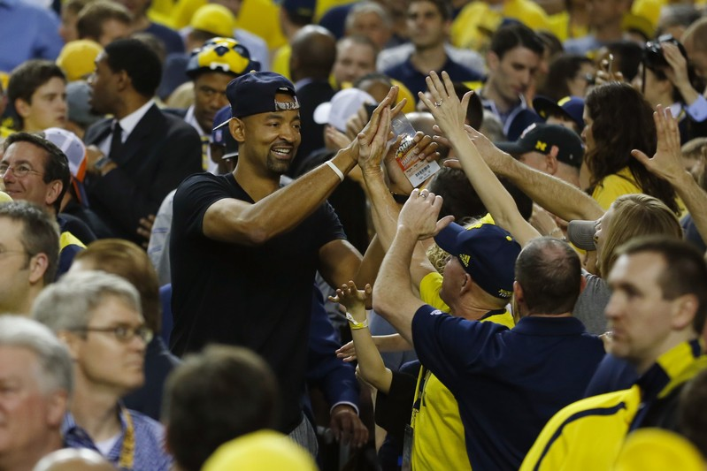 Miami Heat NBA player Juwan Howard celebrates with fans ahead of the Michigan Wolverines' NCAA men's Final Four championship basketball game against the Louisville Cardinals in Atlanta