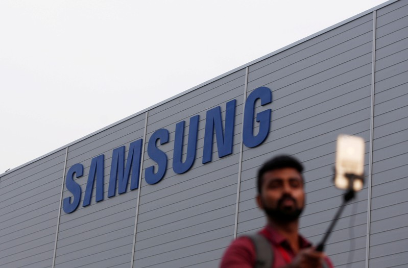 FILE PHOTO: A journalist uses a mobile phone as he works outside the Samsung Electronics smartphone manufacturing facility in Noida