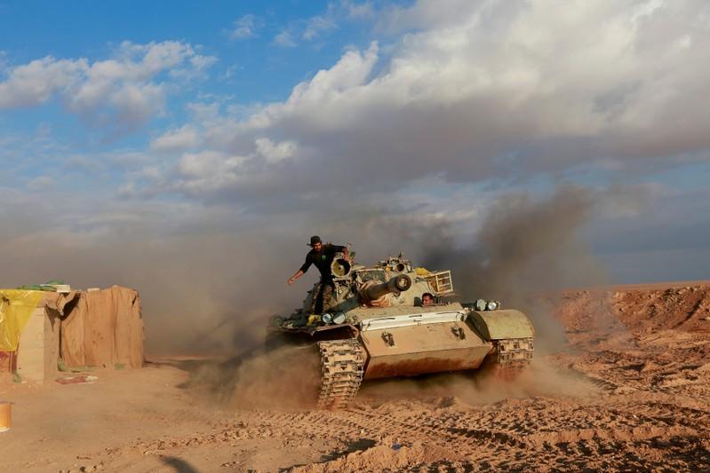 FILE PHOTO: PMF fighters ride in a tank near the Iraqi-Syrian border in al-Qaim, Iraq.