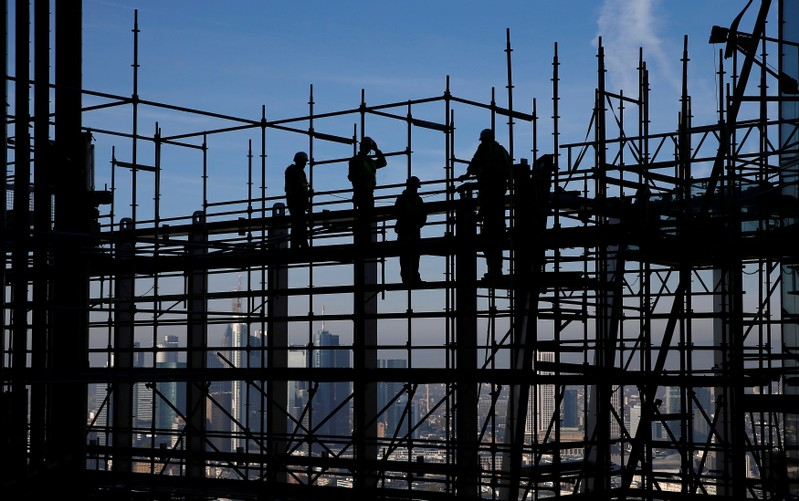 FILE PHOTO: Construction workers are silhouetted while standing on scaffolding at the construction site of the new headquarters of the ECB during a guided media tour in Frankfurt
