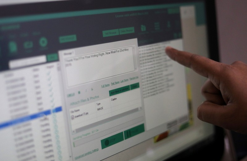 Rohitash Repswal shows a software tool that appears to automate the process of sending messages to WhatsApp users, on a screen inside his office in New Delhi