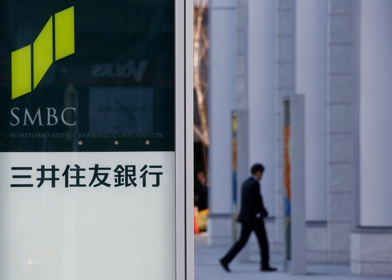 FILE PHOTO: Workers clean windows next to a signboard of Sumitomo Mitsui Financial Group's SMBC Friend Securities in Tokyo