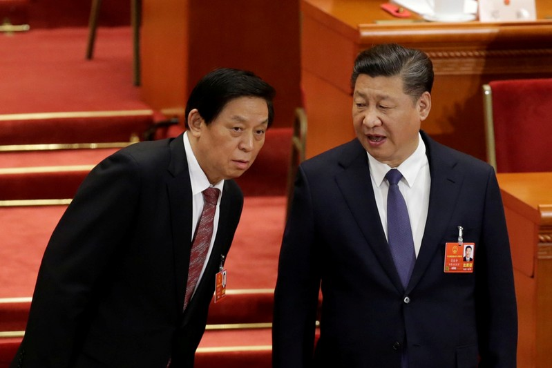 FILE PHOTO: Chinese President Xi Jinping speaks with Chinese Politburo Standing Committee member Li Zhanshu at the third plenary session of the National People's Congress (NPC) at the Great Hall of the People in Beijing