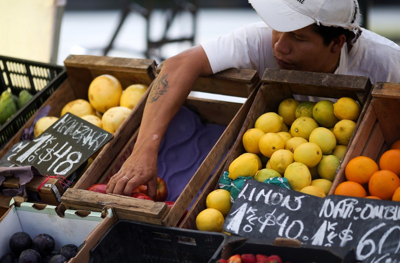 FILE PHOTO: A vegetable seller grabs an apple at a street market