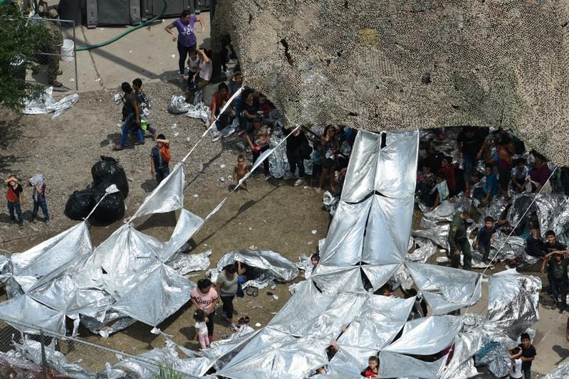 Migrants are seen outside the U.S. Border Patrol McAllen Station in a makeshift encampment in McAllen