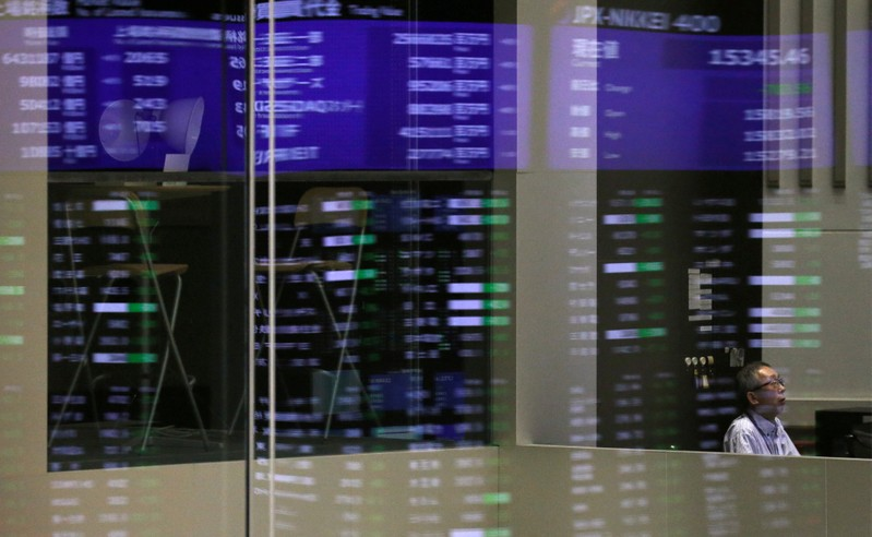 FILE PHOTO: Market prices are reflected in a glass window at the TSE in Tokyo