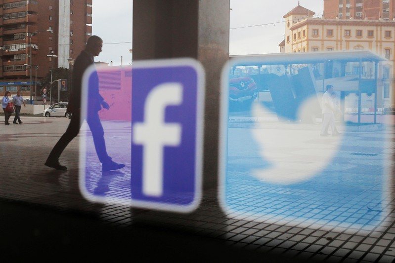 FILE PHOTO: Facebook and Twitter logos are seen on a shop window in Malaga