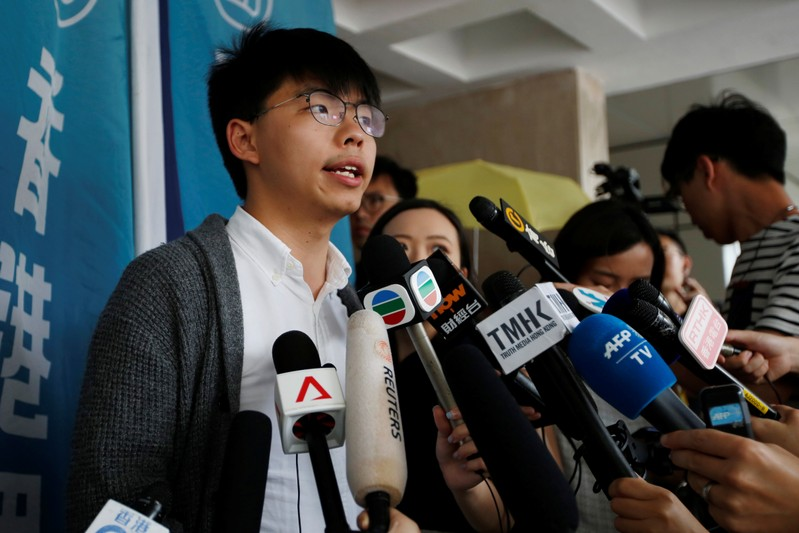 Hong Kong's pro-democracy activist Joshua Wong speaks to members of the media at the High Court in Hong Kong
