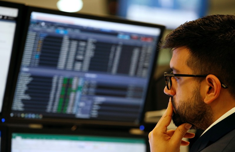 Trader works at his desk whilst screens show market data at CMC Markets in London