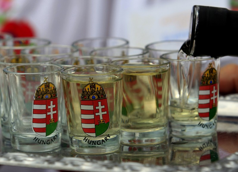 A man fills up glasses with 'palinka', a Hungarian fruit brandy, during the International Wheat Harvest Festival in Opalyi