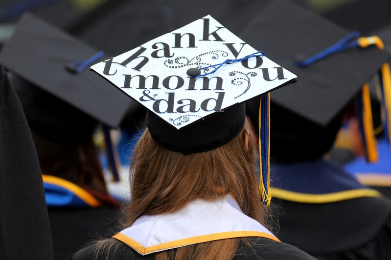FILE PHOTO: Messages and artwork are pictured on the top of the caps of graduating students during their graduation ceremony at UC San Diego in San Diego
