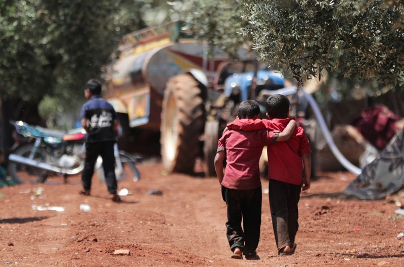 Displaced Syrian children walk together in an olive grove at Atmeh town, Idlib province