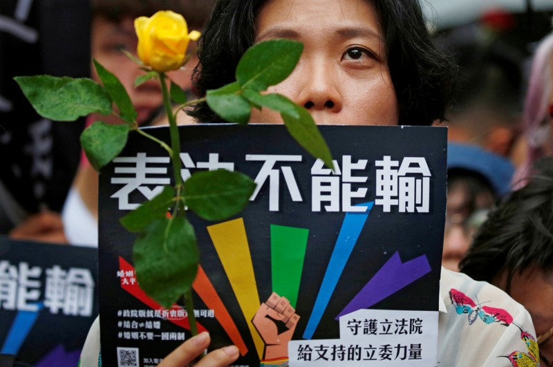 A same-sex marriage supporter holds rose to mourn those who committed suicide due to discrimination during a parliament vote on three draft bills of a same-sex marriage law, outside the Legislative Yuan in Taipei