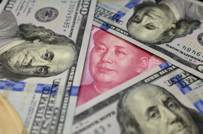 FILE PHOTO: U.S. 100 dollar banknotes and a Chinese 100 yuan banknote are seen in this picture illustration in Beijing, China