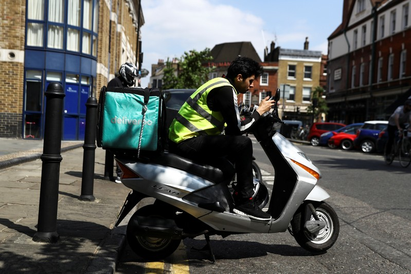 A Deliveroo scooter driver takes a break between deliveries in London