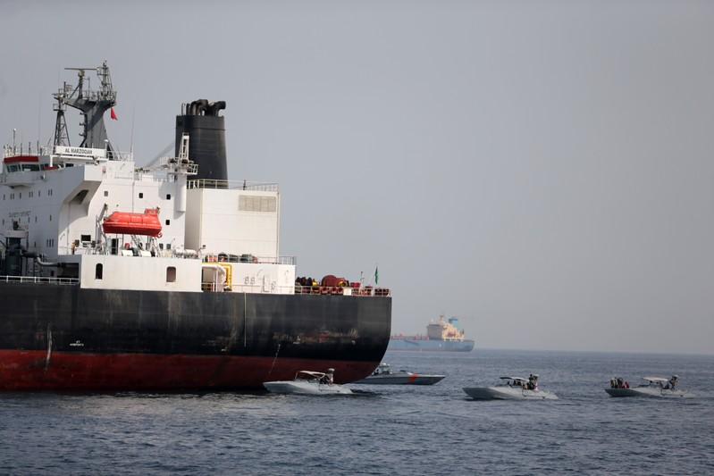 UAE Navy boats are seen next to Al Marzoqah, Saudi Arabian tanker, off the Port of Fujairah