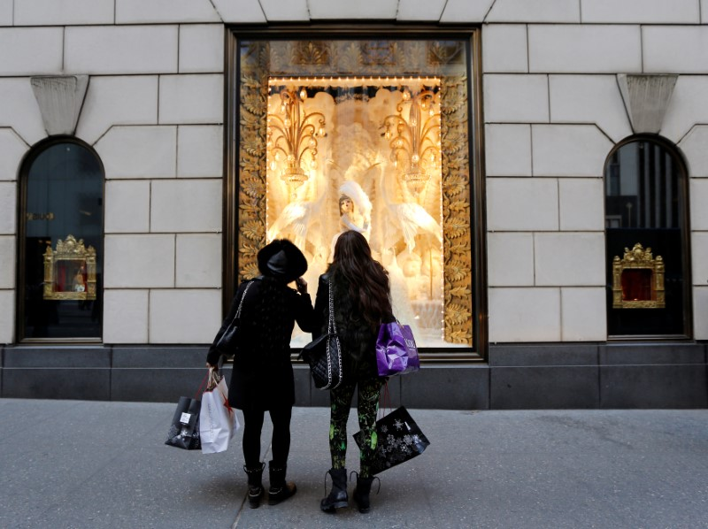 Holiday shoppers look at store windows at Henri Bendel store on 5th Avenue in New York