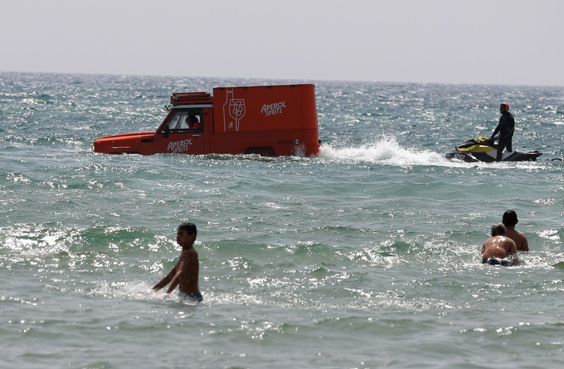 Swimmers look at a boat disguised as a delivery van after it carried out a publicity stunt in the sea on the eve of Eurovision final in Tel Aviv