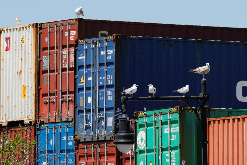 Sea gulls sit on a lamppost beside shipping containers stacked at the Paul W. Conley Container Terminal in Boston
