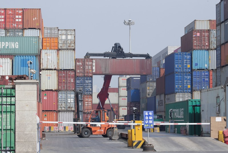 A container is carried onto a truck in a logistics center near Tianjin Port