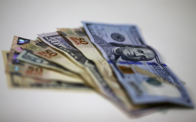 FILE PHOTO: Brazilian Real and U.S. dollar notes are pictured at a currency exchange office in Rio de Janeiro