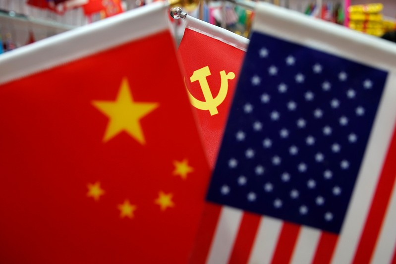 The flags of China, U.S. and the Chinese Communist Party are displayed in a flag stall at the Yiwu Wholesale Market in Yiwu