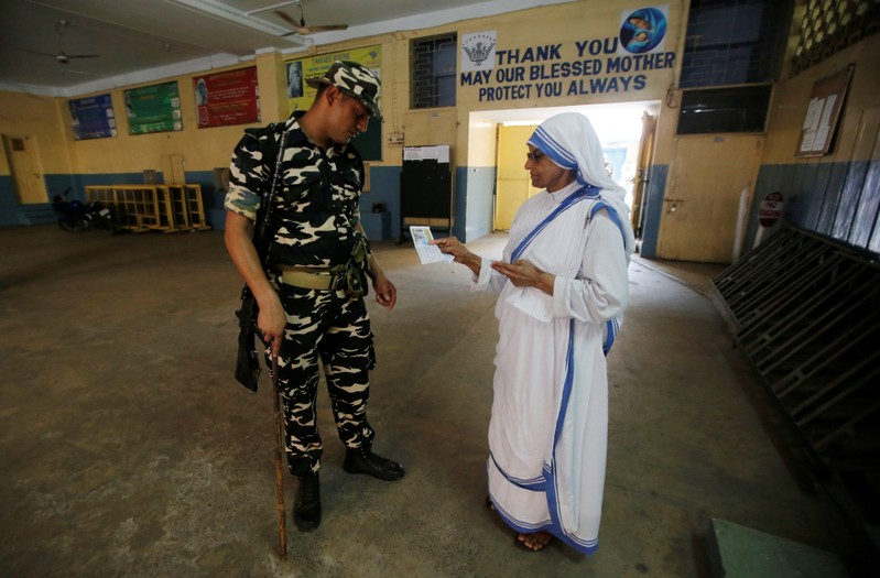 A security personnel checks an identity card of a catholic nun from the Missionaries of Charity as she arrives to cast her vote at a polling station during the final phase of general election in Kolkata