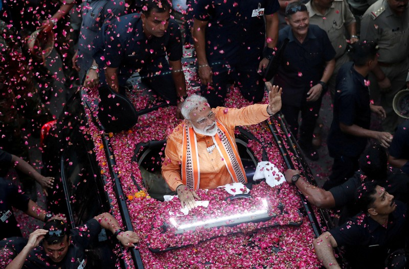 FILE PHOTO: India's Prime Minister Narendra Modi waves towards his supporters during a roadshow in Varanasi