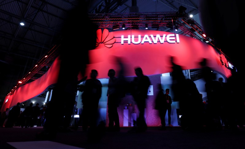 FILE PHOTO: Visitors walk passes Huawei's booth during the Mobile World Congress in Barcelona