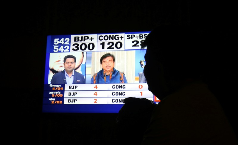 A man looks at a television screen showing exit poll results after the last phase of the general election in Ahmedabad