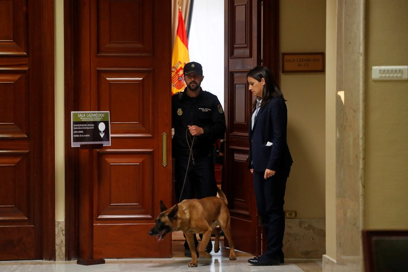 A police officer walks out with a dog from a room where four jailed Catalan politician will get their parliamentary credentials, in Madrid