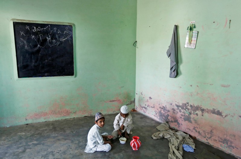 Muslim children eat their lunch during a break at a madrasa or religious school in village Nayabans
