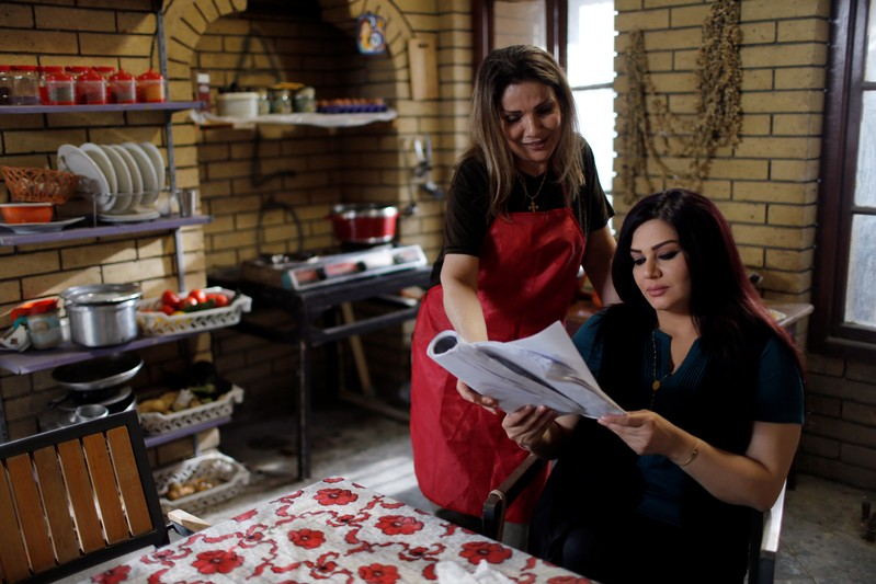 Iraqi actors read their scripts to prepare for a scene of Òthe hotelÓ TV series, which is being filmed and broadcast during the Muslim holy month of Ramadan, in Baghdad