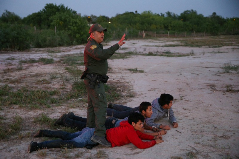 Border patrol agent Sergio Ramirez apprehends immigrants who illegally crossed the border from Mexico into the U.S., near McAllen