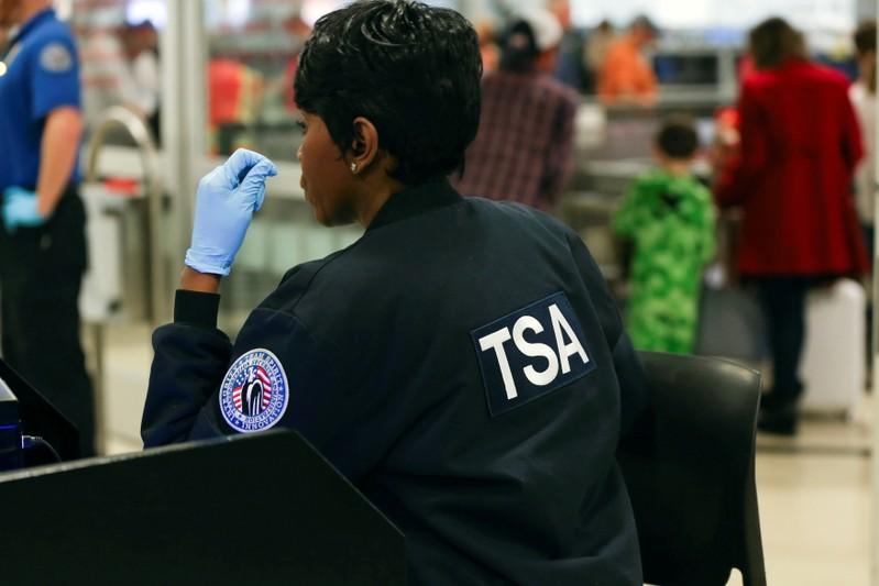 FILE PHOTO - A TSA agent screens passengers at a security checkpoint at Hartsfield-Jackson Atlanta International Airport amid the partial federal government shutdown, in Atlanta